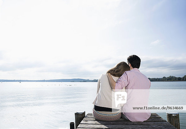 Romantic couple hugging lake jetty tranquil