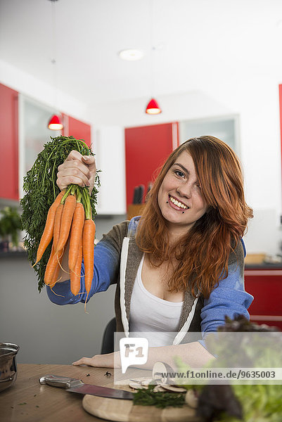 Young woman holding bunch of carrots at kitchen
