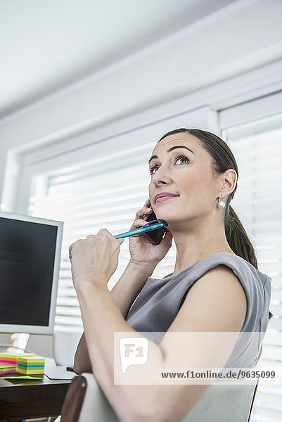 Businesswoman working on computer and talking on mobile phone
