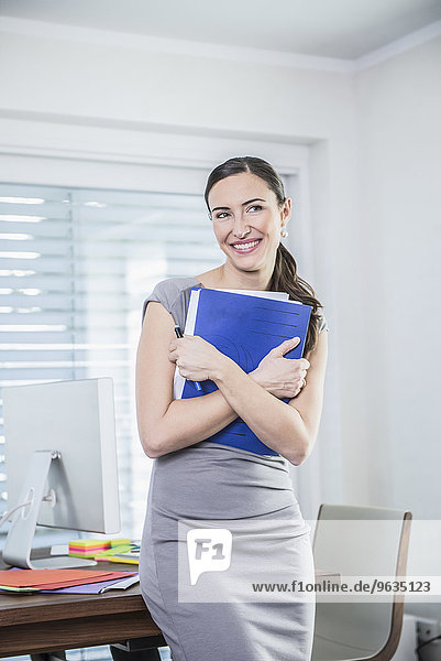 Businesswoman holding files and standing against a table in an office