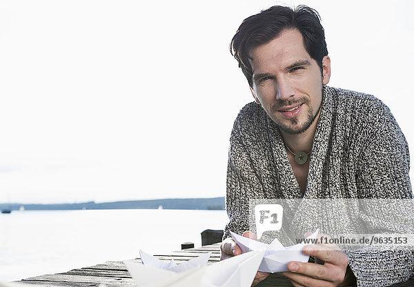 Close up portrait man holding paper boat
