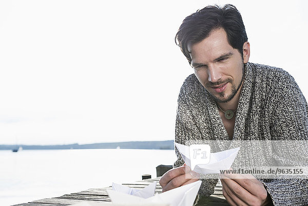 Young man building playing paper boat