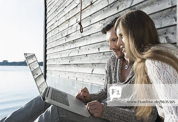 Man woman using laptop computer outdoors