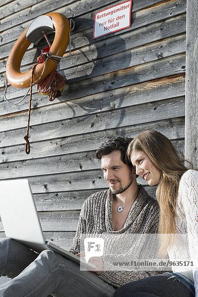 Portrait young couple using laptop outdoors