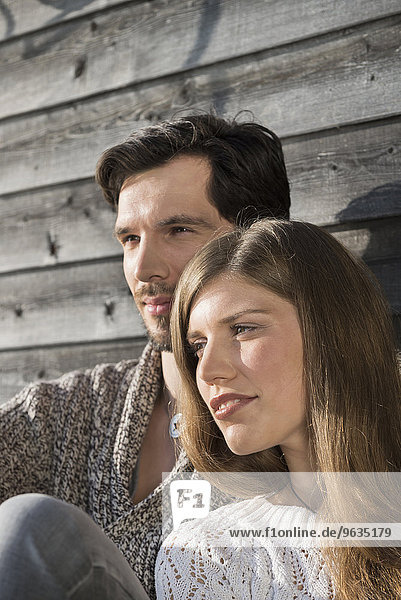 Portrait couple close up relaxing wooden wall