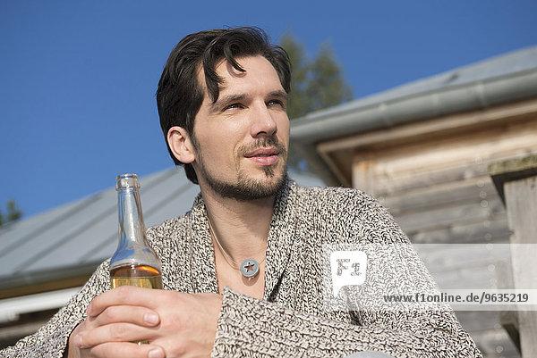 Close up portrait man holding beer bottle