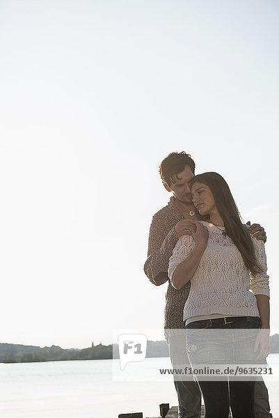 Young couple embracing sunset lake romantic