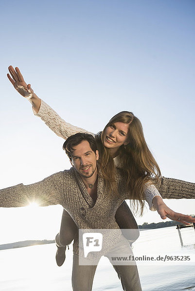Young happy couple fun dancing piggyback sunset
