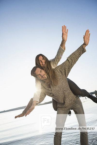 Young couple woman riding piggyback sunset