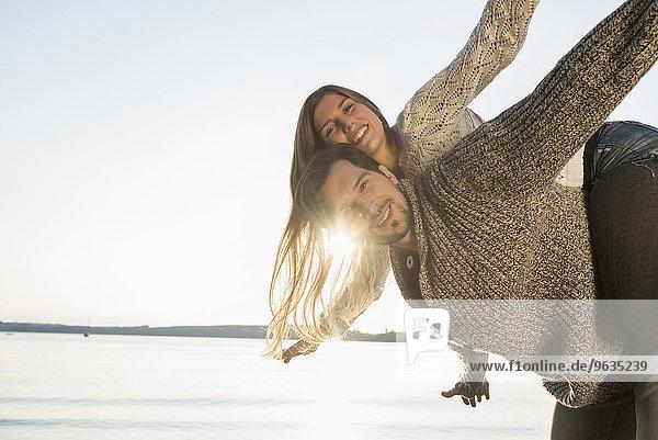 Sunset fun woman riding piggyback man