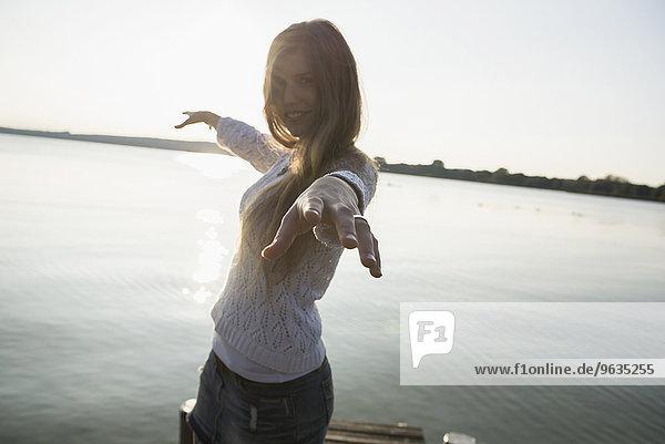 Lake young pretty woman dancing sunset