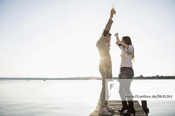 Lake sunset jetty young couple dancing