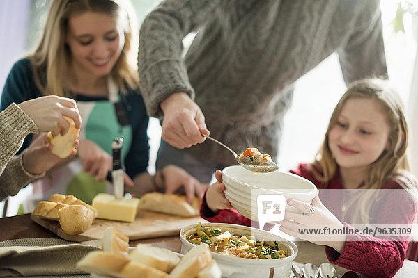 sitzend stehend Mann 4 Mensch Menschen geben Lebensmittel Schüssel Schüsseln Schale Schalen Schälchen Tisch