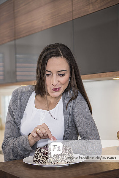 Woman eating cake in a kitchen