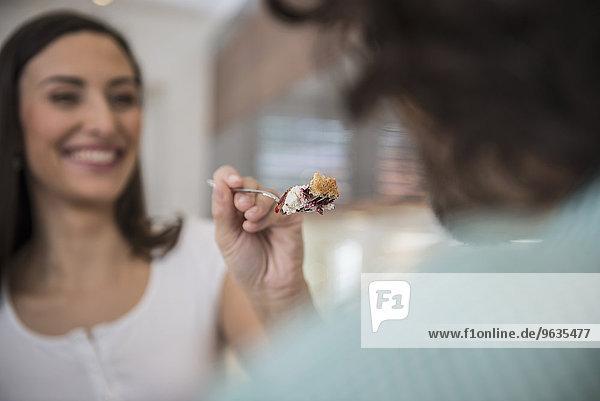 Woman feeding slice of cake to her husband Woman feeding slice of cake to her husband