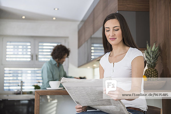 Woman reading a newspaper while her husband cooking in a kitchen