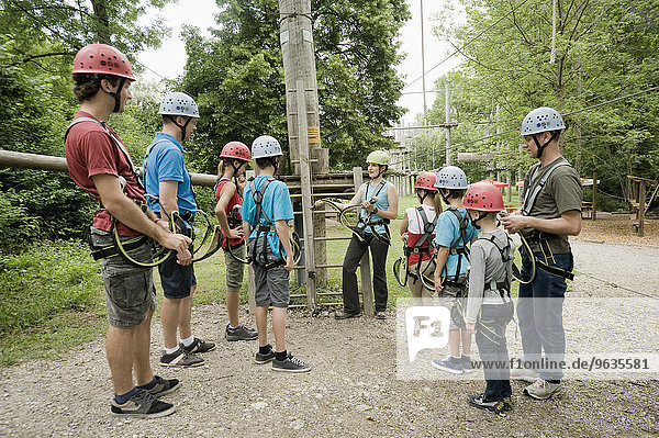 Young woman giving instruction to group of people for climbing crag