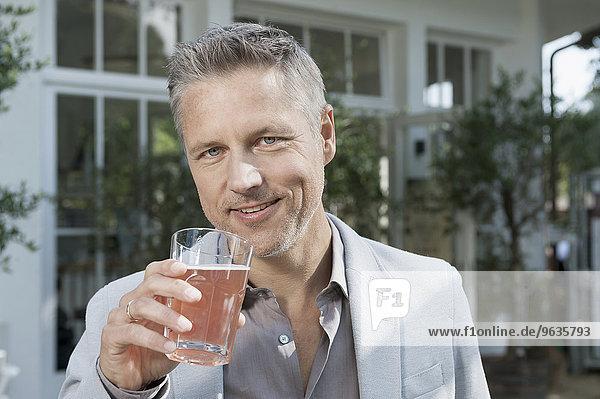 Businessman portrait smiling drinking fruit juice