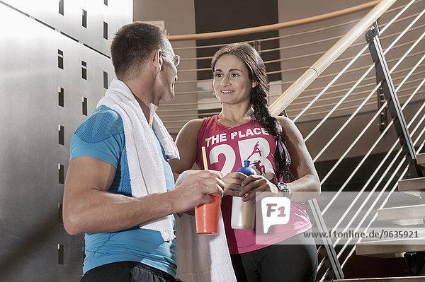 Fit couple fitness studio taking a break talking