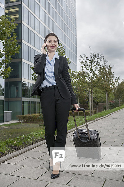Businesswoman pulling luggage while calling with mobile phone