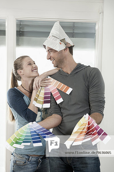 Couple choosing colour samples and smiling