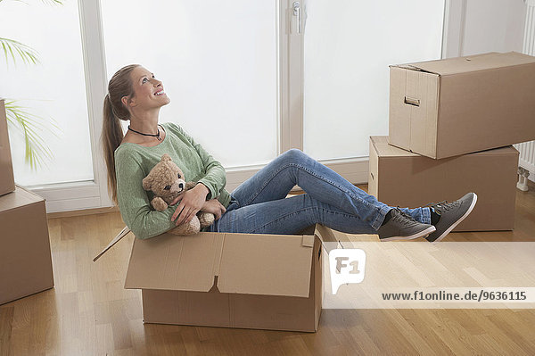 Young woman sitting in a cardboard box and dreaming about her new home