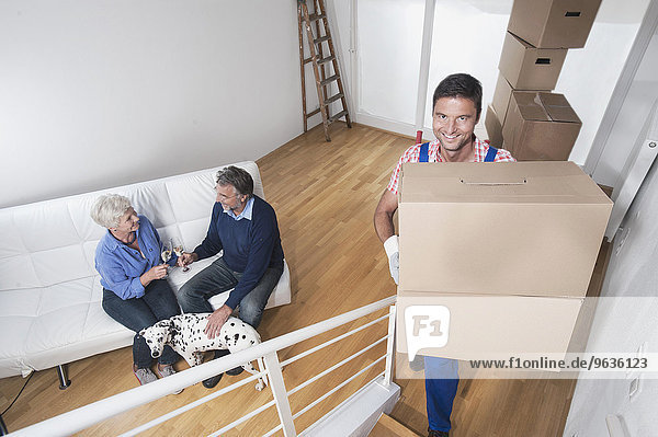 Removal man moving cardboard box upstairs and senior couple celebrating with champagne in new home