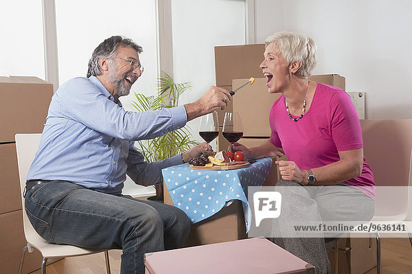 Senior man feeding food to his wife in new home