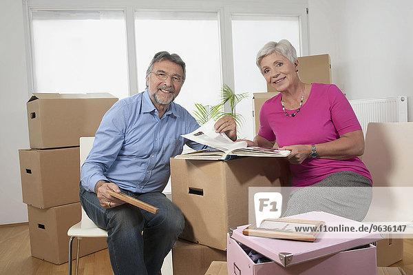 Senior couple looking at photo album in new apartment