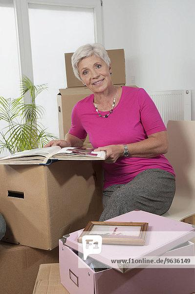 Senior woman with photo album in new apartment