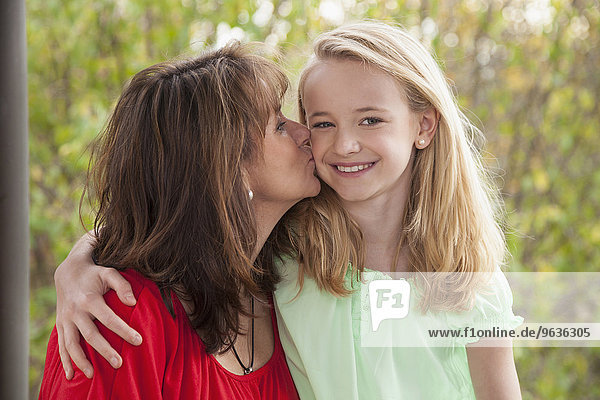 Woman kissing her daughter