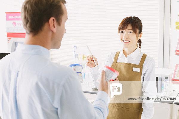 Junge japanische Frau arbeitet am Supermarkt