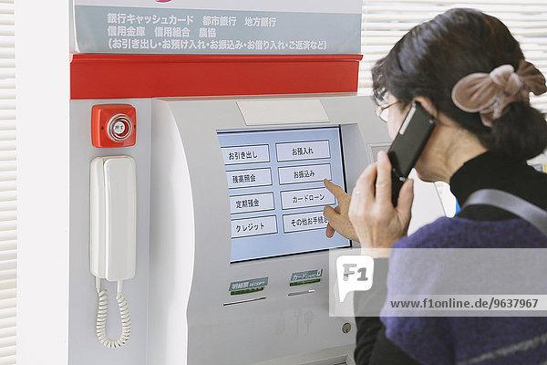 Japanische Frau mit Geldautomaten in einem Supermarkt