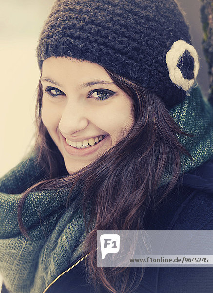 Smiling young woman wearing hat and scarf in winter  portrait