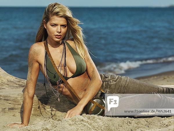 Junge Frau mit Jeans und Bikini-Oberteil liegt an einem Sandstrand
