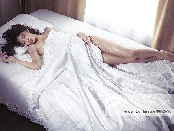 Junge Frau schläft in einem Bett  von Bettlaken bedeckt