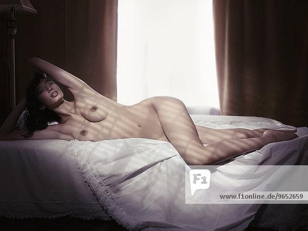 Nackte Frau liegt in einem Bett