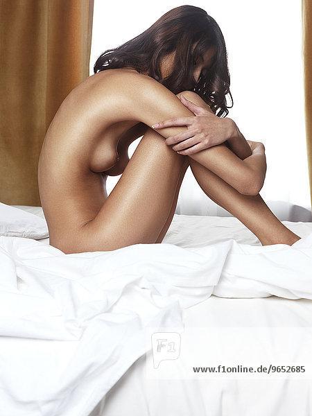 Nackte Frau sitzt auf einem Bett