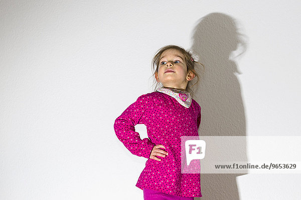 Girl  3 years  wearing a pink shirt  looking arrogant  casting a shadow on a white wall