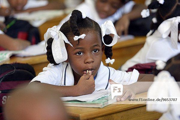 Schoolgirl in class,  Basile Moreau Primary School,  Carrefour,  Port-au-Prince,  Ouest Department,  Haiti,  North America *** IMPORTANT: No publication by charities! ***