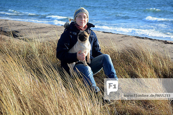 Young woman wearing winter clothes and holding a pug  sitting in dry grass at the Baltic Sea  Scania  Sweden  Europe