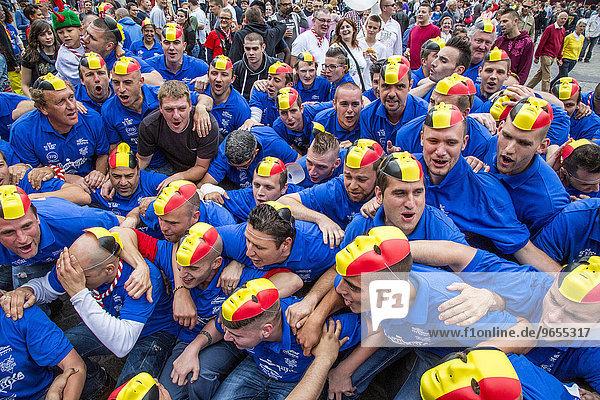 Menschenmenge mit belgischer Flagge als Maske auf dem Kopf  Stadtfest Doudou auf dem Grand Place  Mons  Belgien  Europa