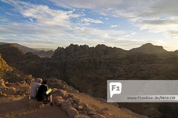 Paar mit Blick über die Felsen nahe Petra in der Dämmerung  Jordanien  Vorderasien  Asien