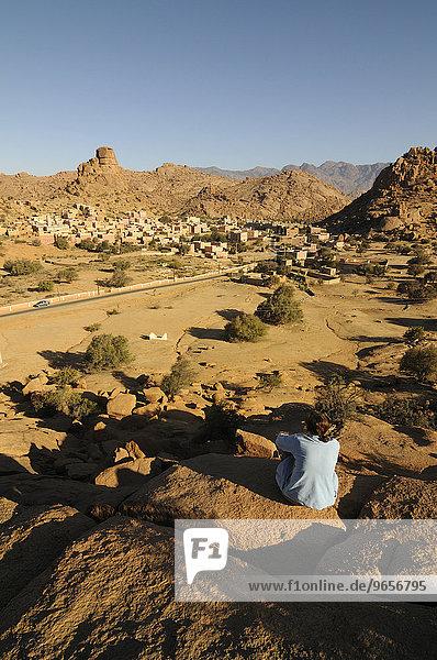 Touristin entspannt sich vor einem malerischen Bergdorf bei Tafraoute  Südmarokko  Marokko  Afrika