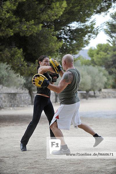 Ein Mann und eine Frau trainieren Kampfsport in einem Park