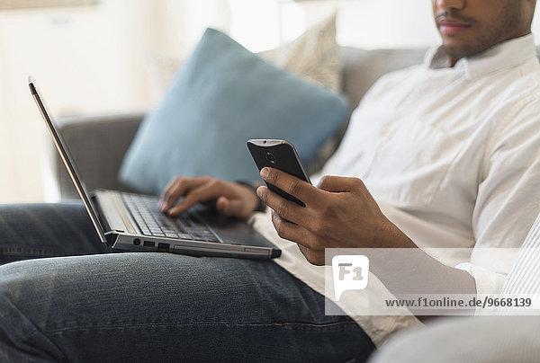Handy sitzend benutzen Mann Notebook Zimmer Wohnzimmer