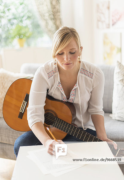 Woman sitting on sofa with acoustic guitar and writing