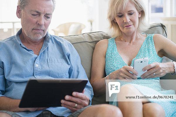 sitzend benutzen Portrait Couch Tablet PC Smartphone
