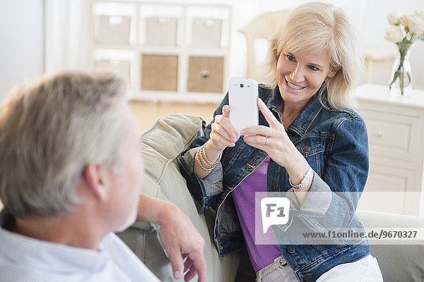 Portrait of woman photographing man with smartphone  sitting on sofa