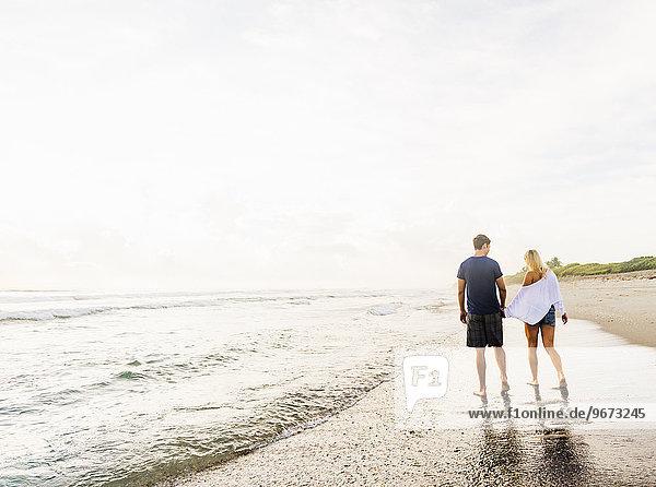Hände halten Händchen halten händchenhaltend Hand in hand gehen Strand Sand jung vorwärts Linie Brandung